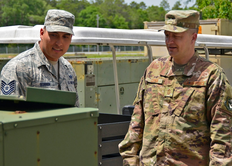 Chief Master Sgt. James Loper, 10th Air Force Command Chief, listens as Tech. Sgt. William Bonner, 919th Special Operations Communications Squadron, gives him an overview
