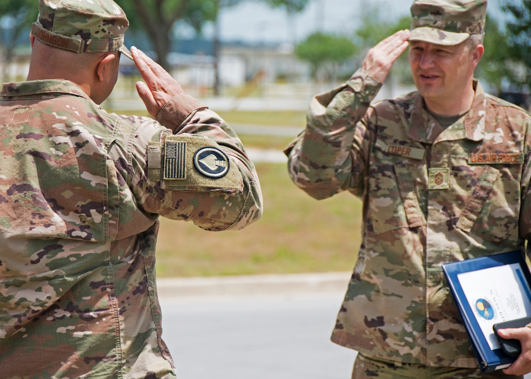 Chief Master Sgt. James Loper, 10th Air Force Command Chief, salutes Lt. Col. Christopher Johnson, 919th Special Operations Communications Squadron commander