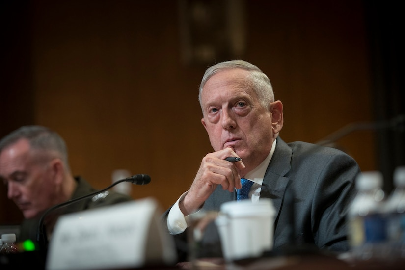 Defense Secretary James N. Mattis sits behind the desk.