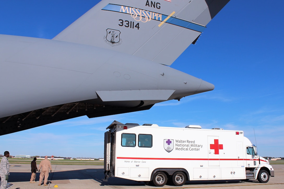 An ambulance bus backs up to the Mississippi Air National Guard C-17 Globemaster III as Airmen prepare to unload patients at Joint Base Andrews, Md., April 26, 2018. The bus transports patients to Walter Reed National Military Medical Center in Bethesda, Md. (U.S. Air Force photo by Karina Luis)