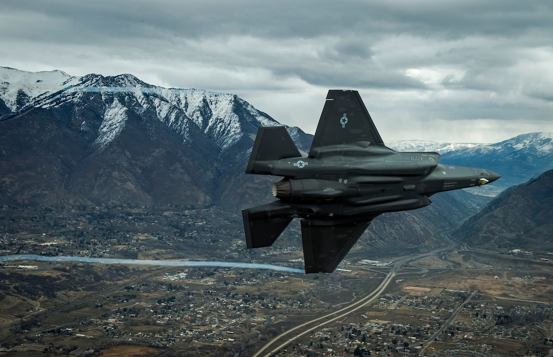 F-35A Aircraft banks in front of mountain background