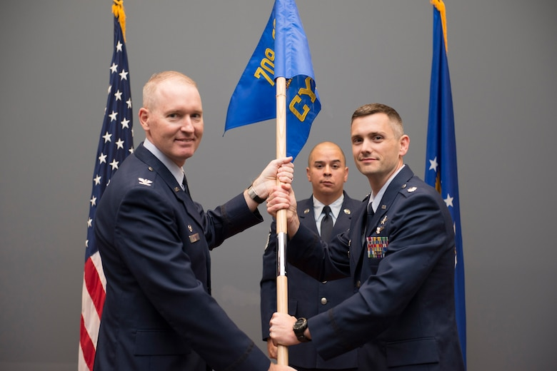 Lt. Col. Nathan Loyd (right), 709th Cyberspace Squadron commander, accepts his squadron's guidon from Col. Richard Mendez, 709th Support Group commander, during a ceremony at the Air Force Technical Applications Center, Patrick AFB, Fla., April 11, 2018.  Loyd assumed command of the newly-formed squadron after the nuclear treaty monitoring center reorganized to improved mission effectiveness.  Pictured in background is Master Sgt. Brian Bowles, ceremonial guidon bearer.  (U.S. Air Force photo by Matthew S. Jurgens)