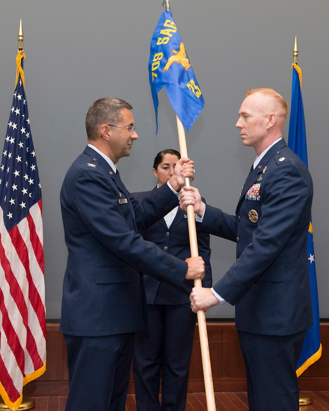 Lt. Col. Jeremy Goodwin (right), 23rd Analysis Squadron commander, accepts his unit's guidon from Col. Jonathan VanNoord, 709th Surveillance and Analysis Group commander during a ceremony in the Doyle M. Northrup Auditorium at the Air Force Technical Applications Center, Patrick AFB, Fla., April 4, 2018.  Goodwin assumed command of the newly formed squadron after the nuclear treaty monitoring center reorganized to improve mission effectiveness.  (U.S. Air Force photo by Matthew S. Jurgens)