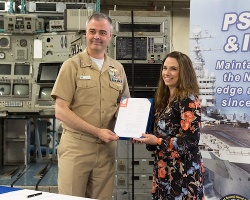 Captain Howard Markle, commander of Puget Sound Naval Shipyard & Intermediate Maintenance Facility, and U.S. Naval Undersea Museum Director Lindy Dosher officially transfer ownership of the control room from the experimental nuclear research submarine NR-1 from the shipyard to the museum during a ceremony in the museum's private storage area May 8, 2018, in Keyport, Washington. (Photo by Carie Hagins, PSNS & IMF photographer)