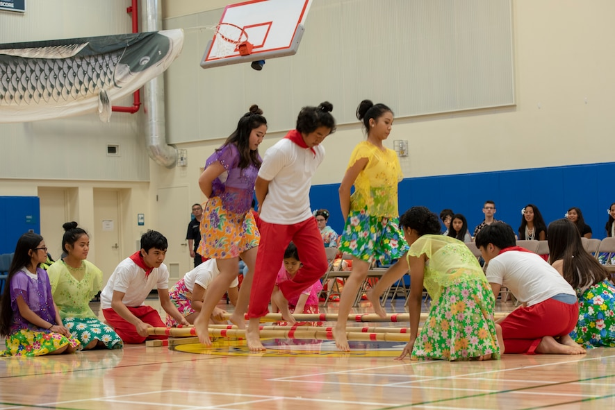 Students perform the Tinikling, a traditional Philippine folk dance, during the National Asian American and Pacific Islander Heritage Celebration at Yokota High School, Yokota Air Base, Japan, May 3, 2018.