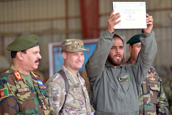 A graduate from UH-60 Mission Qualification Training proudly holds his certificate of training at a graduation ceremony May 8, 2018, Kandahar Air base, Afghanistan. Thirty one Afghan air crew members graduated during the ceremony and are scheduled to begin conducting operational missions almost immediately. (U.S. Air Force photo/1st Lt. Erin Recanzone)