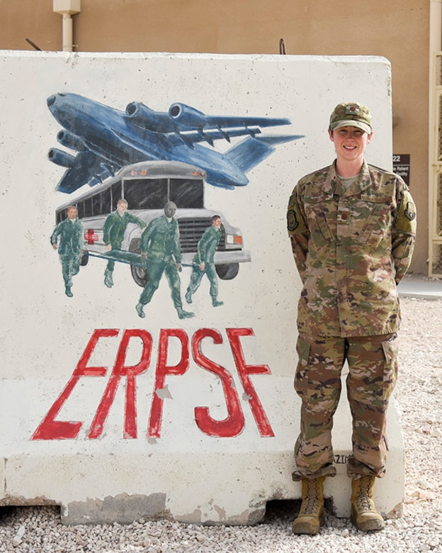 Maj. Kelly Prigge, officer in charge of the En Route Patient Staging Flight (ERPSF), stands in front of the ERPSF t-wall at Al Udeid Air Base, Qatar on May 5, 2018. The ERPSF plays a vital role in transporting patients from various deployed location and ensuring their safe and stable transport to a facility that can support the sustained injuries. (U.S. Air Force photo by Staff Sgt. Enjoli Saunders)