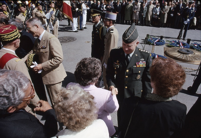 U.S. Army Gen. Crosbie Edgerton Saint, commander of U.S. Army Europe and commander of Central Army Group, shakes hands with attendees during a D-Day ceremony in an undisclosed location in June 1990.