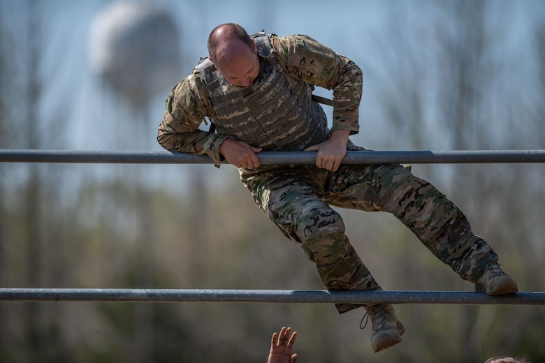 Staff Sgt. John Raven, assigned to 1st Combat Camera Squadron, climbs over a high bar during the obstacle course portion of the 2018 SPC Hilda I. Clayton Best Combat Camera Competition at Marine Corps Base Quantico, Va., May 1, 2018. The competition is an annual event open to all branches of the military, it's hosted by the 55th Signal Company (Combat Camera) in order to test the technical and tactical proficiencies of Defense Department combat photographers. (U.S. Army photo by Staff Sgt. Pablo N. Piedra)