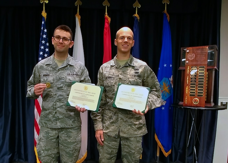 Tech. Sgt. Thomas Grimes and Staff Sgt. Corban Lundborg, both assigned to the 4th Combat Camera Squadron, display their award certificates and coins after being announced as third-place finishers of the 2018 SPC Hilda I. Clayton Best Combat Camera Competition during an award ceremony at Ft. George G. Meade, Md., May 4, 2018. The competition is an annual event open to all branches of the military, it's hosted by the 55th Signal Company (Combat Camera) in order to test the technical and tactical proficiencies of Defense Department combat photographers. (U.S. Air Force photo by Maj. Zach Anderson)