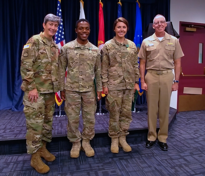 Senior Airman Maygan Straight and Airman 1st Class Franklin Harris, both assigned to 1st Combat Camera Squadron, are congratulated by Army Col. Karen J. Roe, 21st Signal Brigade commander, and Navy Cmdr. Thomas H. Cotton, Defense Media Activity Joint Combat Camera program manager, after being announced as winners of the 2018 SPC Hilda I. Clayton Best Combat Camera Competition during an award ceremony at Ft. George G. Meade, Md., May 4, 2018. The competition is an annual event open to all branches of the military, it's hosted by the 55th Signal Company (Combat Camera) in order to test the technical and tactical proficiencies of Defense Department combat photographers. (U.S. Air Force photo by Maj. Zach Anderson)
