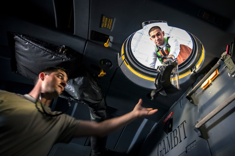 Airman 1st Class Jesse Orosco, right, 71st Aircraft Maintenance Unit (AMU) crew chief, passes a protectant helmet to Staff Sgt. Ryan Culbertson, 71st AMU crew chief, during an HC-130J Combat King II wash, May 7, 2018, at Moody Air Force Base, Ga. Upon return from a deployment or every 180 days, HC-130's are thoroughly cleaned and inspected as part of routine upkeep and to ensure its respective components are in working condition. (U.S. Air Force photo by Airman 1st Class Eugene Oliver)