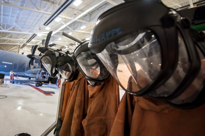 Protective masks and body suits rest on hangers during an HC-130J Combat King II wash, May 8, 2018, at Moody Air Force Base, Ga. Upon return from a deployment or every 180 days, HC-130's are thoroughly cleaned and inspected as part of routine upkeep and to ensure its respective components are in working condition. (U.S. Air Force photo by Airman 1st Class Eugene Oliver)