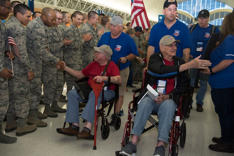 """Veterans shake the hands of Airmen and supporters while being pushed by Honor Flight San Antonio volunteer """"Guardians"""" May 5, 2018 ."""