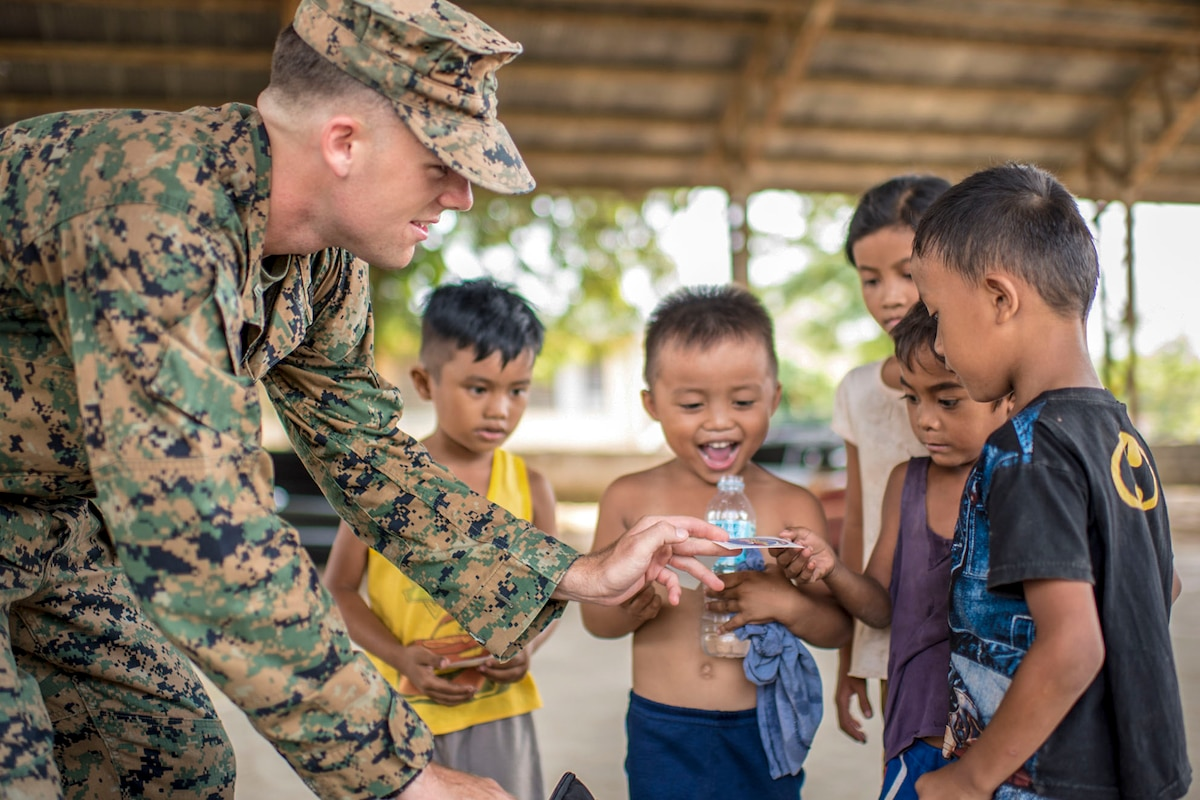 A Marine hands a sticker to a little boy, as others gather around smiling.