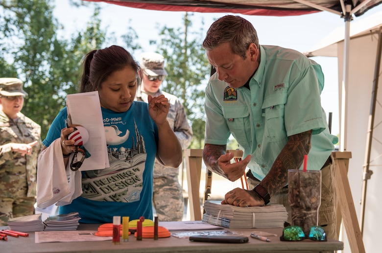 Evelyn Walters, Team Shaw spouse, left, speaks with Marty Long, 20th Force Support Squadron Skeet and Trap Range manager, during the Outdoor Recreation open house at Shaw Air Force Base, S.C., May 9, 2018.