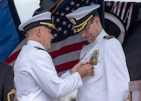 Capt. Richard Seif, commander, Submarine Squadron One, presents a Legion of Merit to Cmdr. Eric J. Rozek, commanding officer of the Virginia-class fast-attack submarine USS Mississippi (SSN 782), during a change of command ceremony on the submarine piers in Joint Base Pearl Harbor-Hickam, May 8. (U.S. Navy photo by Mass Communication Specialist 2nd Class Michael Lee/Released)