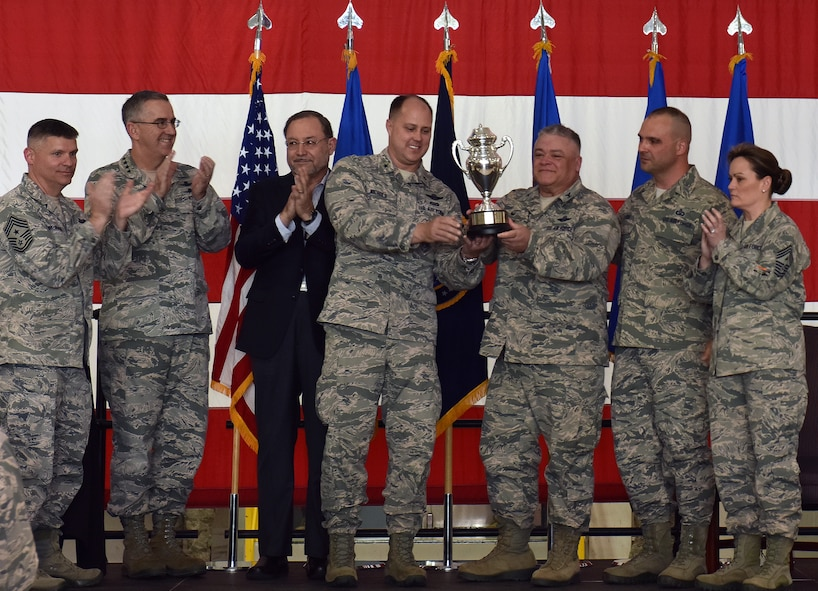 U.S. Air Force Brig. Gen. John Nichols, the 509th Bomb Wing commander, center left, and Col. Ken Eaves, the 131st Bomb Wing commander, display the Omaha Trophy at Whiteman Air Force Base, Mo., May 8, 2018. The award was awarded to Team Whiteman by U.S. Strategic Command and the Strategic Command Council for executing the best Strategic Bomber Operations of 2017. (U.S. Air Force photos by Senior Airman Jovan Banks)