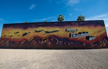 A 20-foot mural stands near the Lightning Gate entrance of Luke Air Force Base, Ariz., May 8, 2018. The mural represents Luke's heritage by highlighting the progression of aviation airpower in the United States Air Force. (U.S. Air Force photo by Airman 1st Class Alexander Cook)