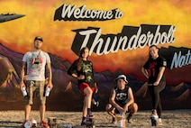 """The team of Thunderbolt artists pose for a group photo in front the """"Welcome to Thunderbolt Nation"""" mural at Luke Air Force Base, Ariz., May 9, 2018. Over the course of a month, the team worked together to complete the mural, which represents Luke's heritage. (U.S. Air Force photo by Airman 1st Class Alexander Cook)"""