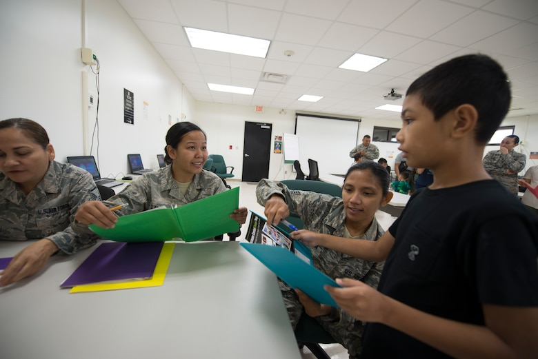 U.S. Air Force Staff Sgts. Kaolanie Claros, center, and Sofia Oropesa, right, both assigned to the U.S. Air Force Reserve's 44th Aerial Port Squadron, introduce military children to readiness activities during Operation Inafa' Maolek at Andersen Air Force Base, May 5, 2018.