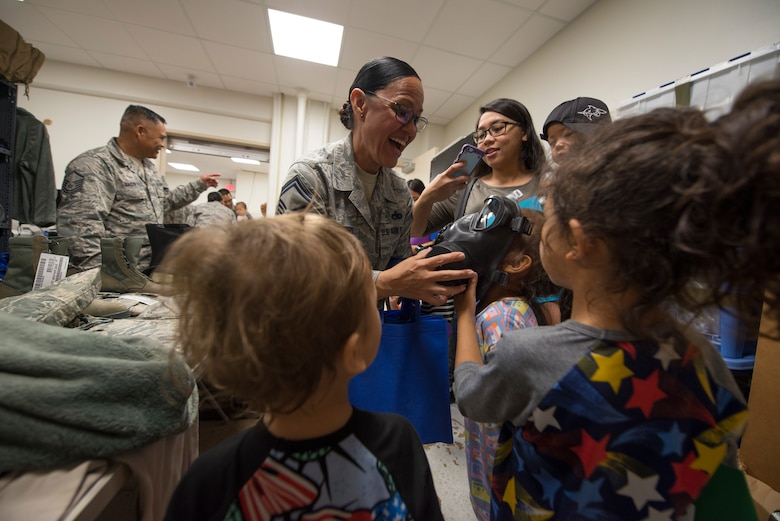 U.S. Air Force Senior Master Sgt. Michelle Quichocho, assigned to the U.S. Air Force Reserve's 44th Aerial Port Squadron, shows military children a gas mask during Operation Inafa' Maolek at Andersen Air Force Base, May 5, 2018.