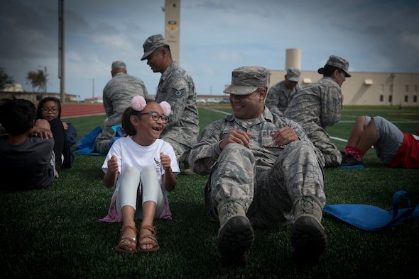 U.S. Air Force Staff Sgt. Joshua Anderson, right, assigned to the U.S. Air Force Reserve's 44th Aerial Port Squadron, performs sit-ups with military children during Operation Inafa' Maolek at Andersen Air Force Base, May 5, 2018.