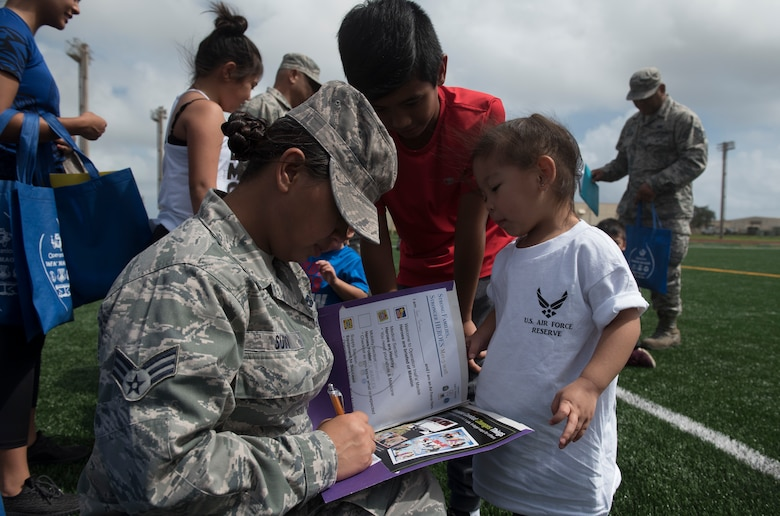 U.S. Air Force Senior Airman Lourkrina M. Sudo, assigned to the U.S. Air Force Reserve's 44th Aerial Port Squadron, signs off military children for their physical fitness portion of Operation Inafa' Maolek at Andersen Air Force Base, May 5, 2018.