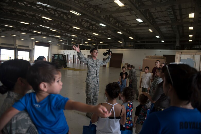 U.S. Air Force Tech. Sgt. Joshua Sablan, assigned to the U.S. Air Force Reserve's 44th Aerial Port Squadron, welcomes military families to the aerial port warehouse during Operation Inafa' Maolek at Andersen Air Force Base, May 5, 2018.