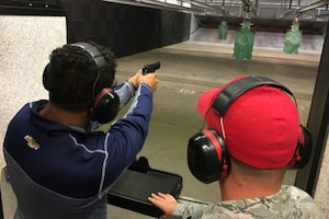 A man shoots a gun at a target while another man watches.