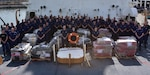 Group photo of the crew of the Coast Guard Cutter James alongside 6 tons of cocaine seized in counterdrug operations.