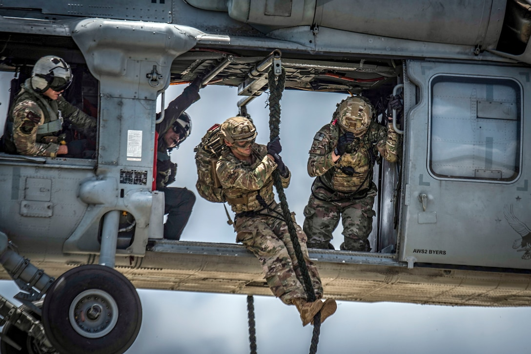 An airman exits a helicopter on a rope as other troops watch from an inside the open aircraft.