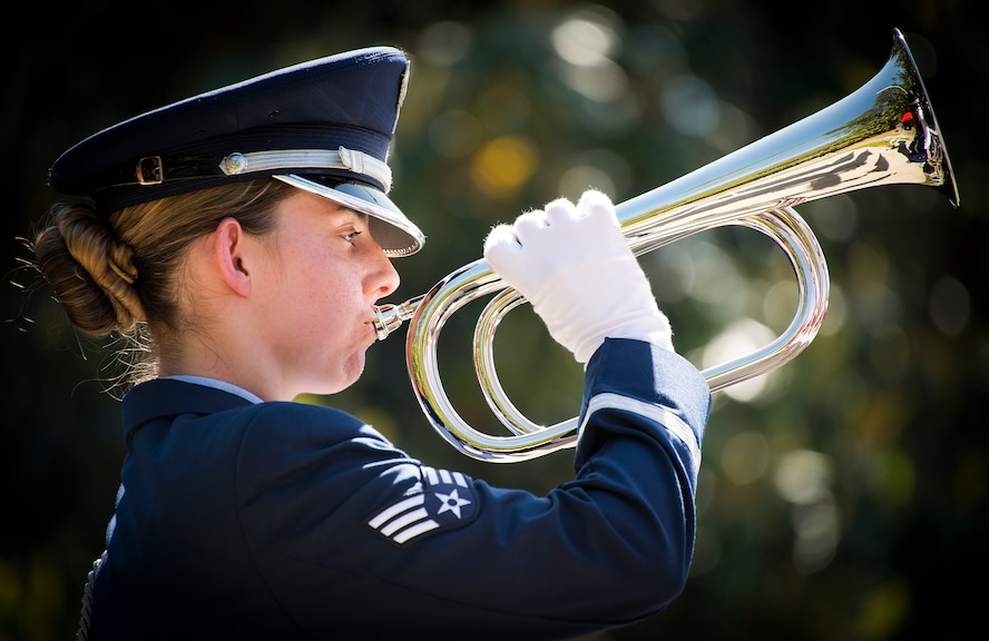 Senior Airman Makayla Scanlan, 96th Surgical Operations Squadron, holds the bugle in place as it plays taps at the 49th Annual Explosive Ordnance Disposal Memorial ceremony May 5, 2018. Names of recent fallen and past EOD technicians are added to the memorial wall and flags presented to their families during a ceremony each year at the Kauffman EOD Training Complex at Eglin Air Force Base, Fla. The Army and Navy added 12 new names this year. The all-service total now stands at 338. (U.S. Air Force photo by Samuel King Jr.)