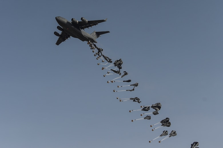 A Qatar Emiri Air Force C-17 Globemaster performs an airdrop during the (QEAF) Lahoub exercise at Al-Qalael dropzone, Qatar, May 9, 2018. The QEAF recently sent one of their C-17 aircrews back to the U.S. to receive airdrop training. This is a new capability for the QEAF and the first C-17 airdrop capability in the Gulf Corporation Council. (U.S. Air Force photo by Staff Sgt. Corey Hook)