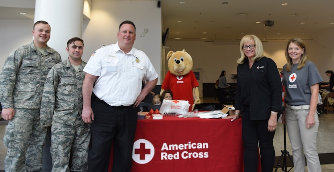 Kaiserslautern Military Community Fire Emergency Services members and American Red Cross members pose in front of their booth at the Kaiserslautern Military Community Center on Ramstein Air Base, Germany, May 11, 2018. The team handed out 200 free smoke detector batteries in an effort to raise awareness about the importance of fire safety.