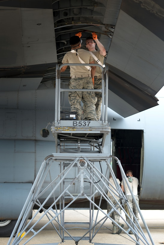 Two men in the Airman Battle Uniform stand on a platform and clean off the inside of a C-130J aircraft wing.