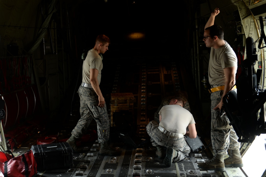 Three men in the Airman Battle Uniform stand in a C-130J aircraft.