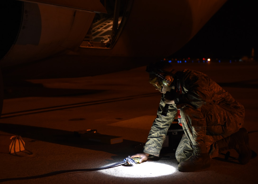 A male works in the dark at night on a C-130J.