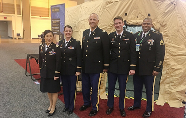 Five medical Soldiers standing front of a medical tent display