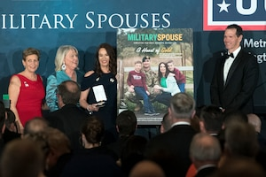 Three women and a man stand around a large poster during the Military Spouse of the Year ceremony.