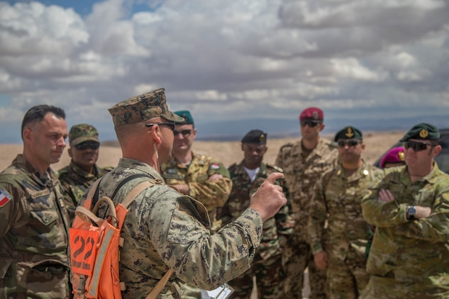 An exercise controller with Tactical Training Exercise Control Group briefs international military officers before a fire support coordination exercise at Observation Post Left aboard the Marine Corps Air Ground Combat Center, Twentynine Palms, Calif., May 2, 2018. The international officers are students at the Command and Staff College, Marine Corps University, Marine Corps Base Quantico, Va., and are set to graduate June 6, 2018. (U.S. Marine Corps photo by Lance Cpl. Preston L. Morris)