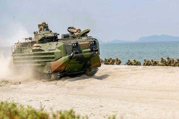 An amphibious vehicle kicks up sand while driving on the beach, as troops crouch in a line nearby.
