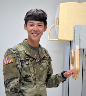 Private Joanna Barton poses in the radiology laboratory at the Medical Education and Training Campus at Joint Base San Antonio-Fort Sam Houston. Barton and her twin sister, Private Jaclynn Barton, are students in the METC Radiology Program. The twins entered the program in March and are set to graduate in September.