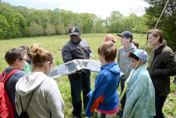 Karl Gullatte, a project manager and community planner with the Center's Engineering Directorate, center, shows fifth-graders a set of working solar panels during Redstone Arsenal's Earth Day outdoor educational event April 19, 2018.