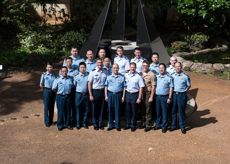 Chinese Maj. Gen. Lan, Deputy Political Commissary/Secretary of Discipline Inspection, People's Liberation Army Air Force (PLAAF) Command College and (Center Right) Brig. Gen. Michael Winkler, Pacific Air Forces (PACAF) Strategy, Plans and Programs director and attendees pose for a photo in the Court Yard of Heroes at Joint Base Pearl Harbor-Hickam, April 26, 2018.