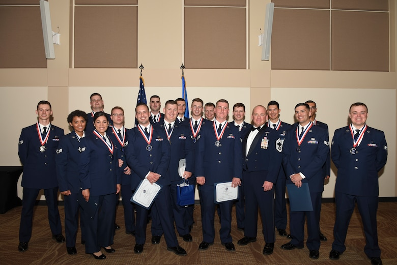 Airman Leadership School class D-18 stand together one final time for a group photo during their graduation May 10, 2018, on Buckley Air Force Base, Colorado. ALS is a 24-day United States Air Force program designed to develop Airmen into effective front-line supervisors. (U.S. Air Force photo by Airman 1st Class Michael D. Mathews)