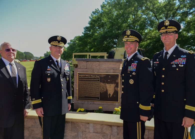 Fort Eustis leaders stand next to a plaque in honor of U.S. Army Sgt. William Wayne Seay at Joint Base Langley-Eustis, Virginia, May 11, 2018. JBLE rededicated Seay Plaza to pay tribute to Vietnam War veterans. (U.S. Air Force photo by Airman 1st Class Monica Roybal)