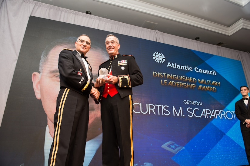 Marine Corps Gen. Joe Dunford stands and presents an award to Army Gen. Curtis M. Scaparrotti as the two shake hands.