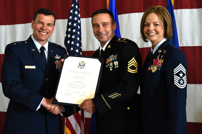 U.S. Air Force Maj. Gen. Matthew Molloy, Air Force Operational Test and Evaluation Center commander, presents U.S. Army Sgt. 1st Class David Fillbrandt, 344th Military Intelligence Battalion platoon sergeant, with a certificate of appreciation at U.S. Air Force Chief Master Sgt. Bobbie Fillbrandt's retirement ceremony in the Louis F. Garland Department of Defense Fire Academy on Goodfellow Air Force Base, Texas, May 10, 2018. This certificate is presented to spouses of military members retiring to show the Air Force's appreciation of their support throughout the military member's career.  (U.S. Air Force photo by Airman 1st Class Seraiah Hines/Released)