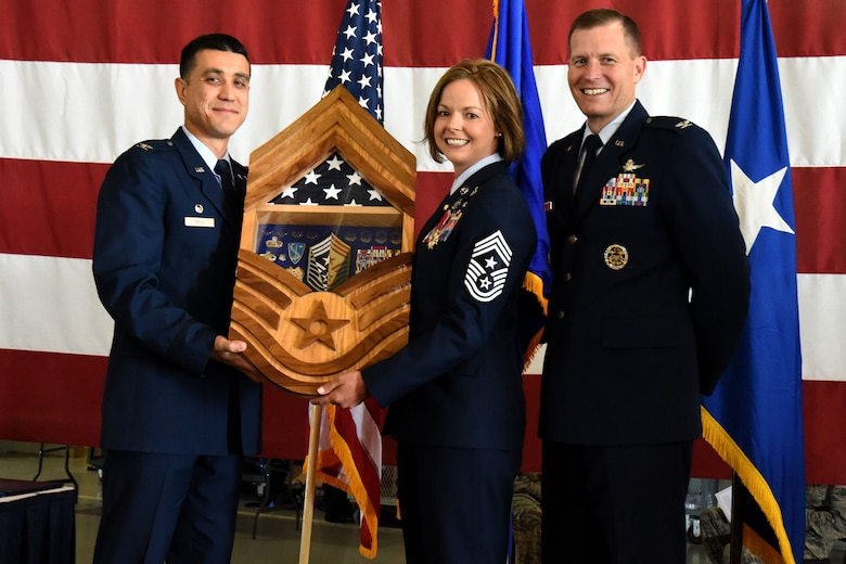U.S. Air Force Col. Ricky Mills, 17th Training Wing commander, and Col. Jeffrey Sorrell, 17th TRW vice commander, present Chief Master Sgt. Bobbie Fillbrandt with a shadow box from the wing in celebration of her retirement at the Louis F. Garland Department of Defense Fire Academy on Goodfellow Air Force Base, Texas, May 10, 2018. The shadow box, designed in the shape of chief's stripes, included symbols of all the ranks in the U.S. Air Force, a folded flag and other various memorabilia from Fillbrandt's career. (U.S. Air Force photo by Airman 1st Class Seraiah Hines/Released)